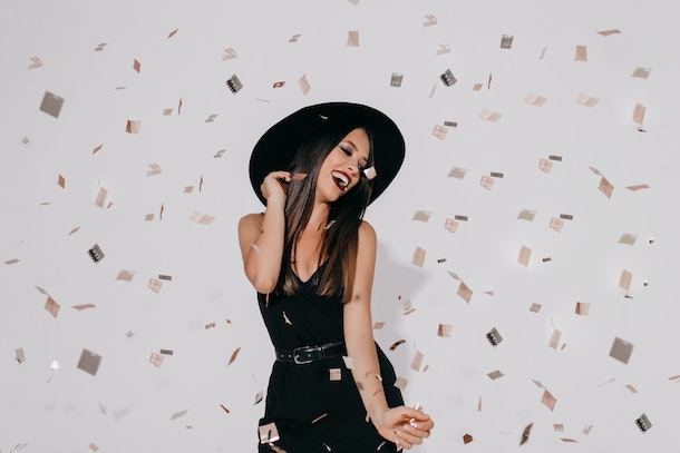Attractive stylish female model in witch costume prepearing for halloween party on isolated background with confetti dancing, having fun, smilimg. Birthday, holiday