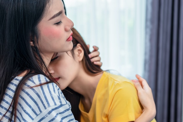 Close up of two Asian Lesbian women embracing together in bedroom. Couple people and Beauty concept. Happy lifestyles and home sweet home theme. Embracing of homosexual. Love scene making of female