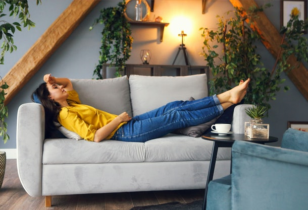 Young brunette woman relaxing on the couch after a long day. Cozy home concept