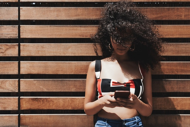 A young caucasian female in the glasses is leaning against a wooden striped wall and typing a message via the smartphone while the wind ruffles her curly bulky hair which cover part of her face