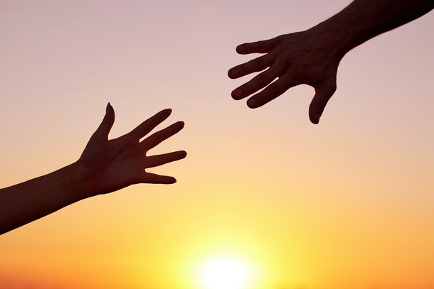 Giving a helping hand.Two hands, man and woman, reaching towards each other at sky sunset.