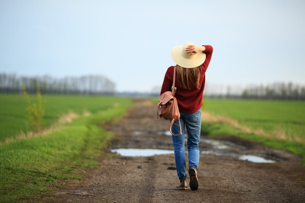 Having sensible shoes while traveling, like this woman who's walking on a dirt road is wearing in the photo, is a great tip.