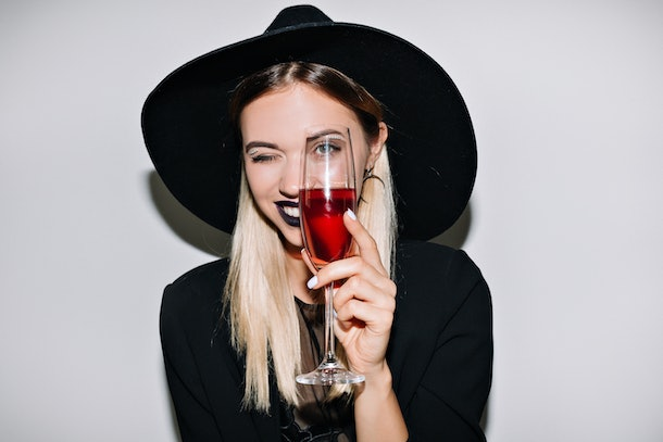 Crazy party time of beautiful woman in elegant black hat with a glass of champagne celebrating new year, birthday, halloween, having fun, dancing,drinking alcohol cocktails.Emotion face, smile