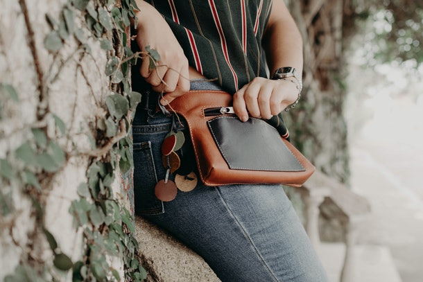 According to travel tips from mom, fanny packs are a great way to keep your valuables safe, like this leather one this woman in the picture is wearing.