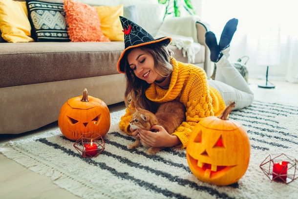 A girl lays on the floor with her cat and carved pumpkins in a chunky yellow sweater and witch hat on Halloween.