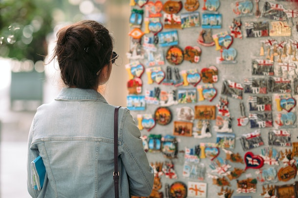 A brunette woman in a denim jacket looks at magnets in a souvenir shop while traveling.