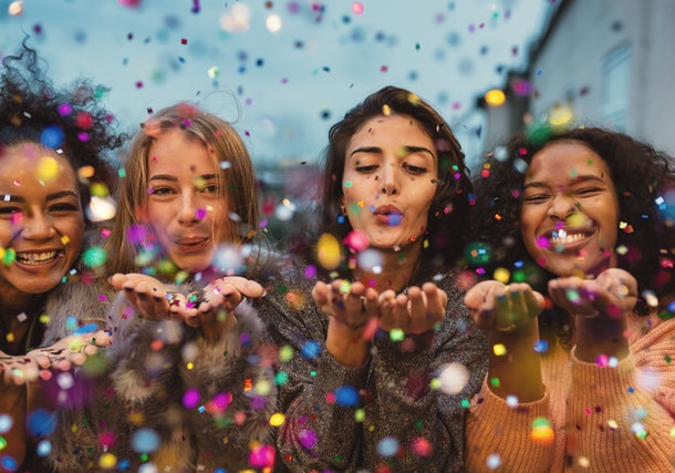 A group of friends blow confetti into the air on New Year's Eve.