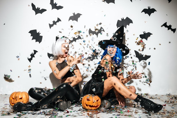 Pumpkin puns for Instagram are great for these two women throwing glitter in the air, dressed up in leather Halloween costumes, with two jack-o'-lanterns by their side.