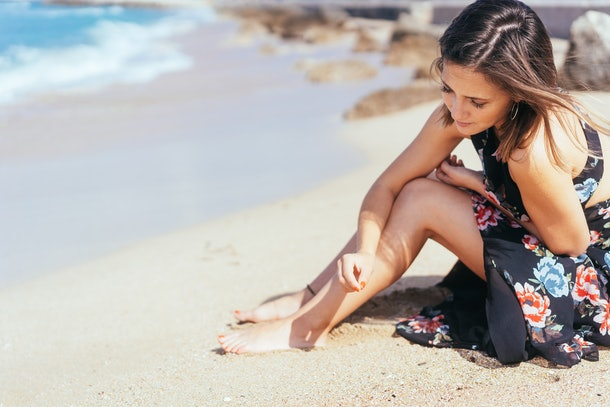 Young woman daydreaming about a person who doesn't love her back and playing with sea sand as she sits on a tropical beach in the warm sunshine