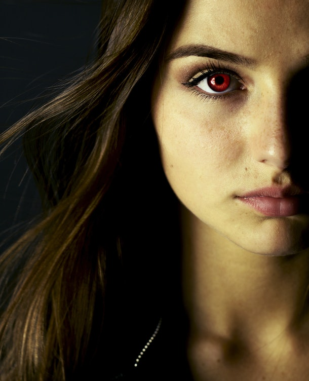 A brunette woman with red eyes is ready to be a vampire for her Halloween costume.
