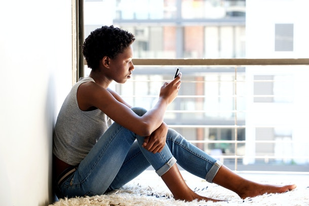 Side portrait of african american female using mobile phone by window at home