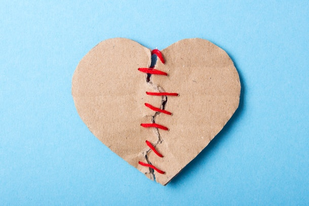 The heart is combined, love is back. A paper heart made of two halves is sewn with a red thread on a blue background