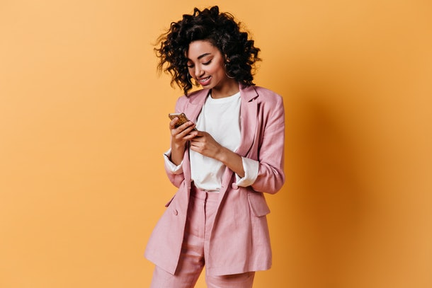 Smiling girl in pink jacket texting message. Glad young woman in suit holding smartphone.