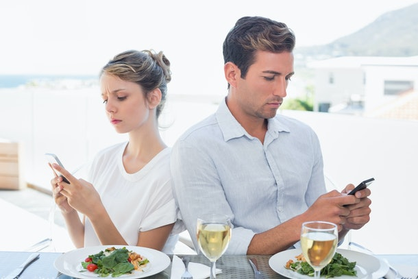 Concentrated young couple text messaging at food table