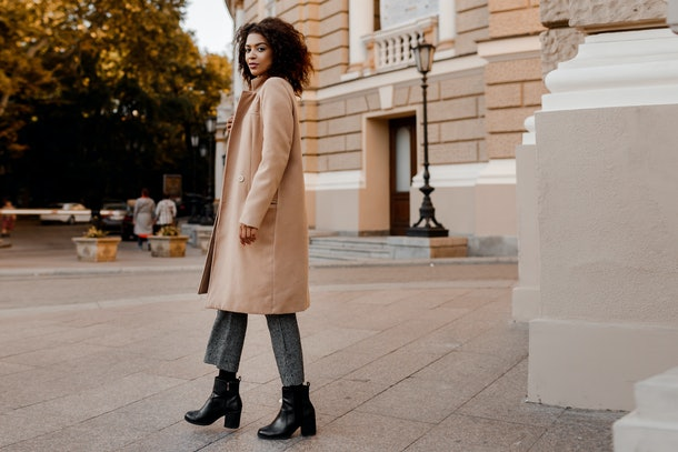 Fashion  full length  image of elegant  black woman in stylish luxury beige coat and velvet sweater, hight heels, walking outdoor.