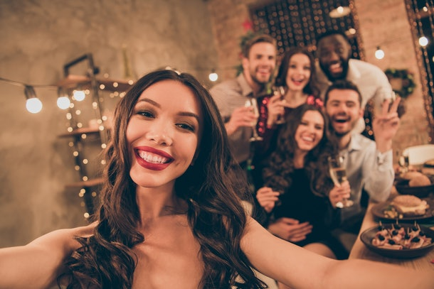Close up photo of cheerful lovers celebrate xmas christmas party make selfie gather around table with feast  in house full of newyear lights indoors