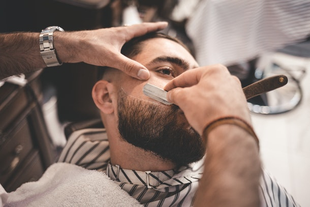 man who has grown a beard gets a shave