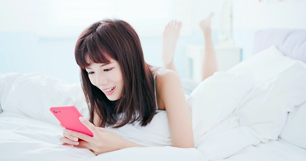 woman text message by smart phone happily and lying in the bed at home