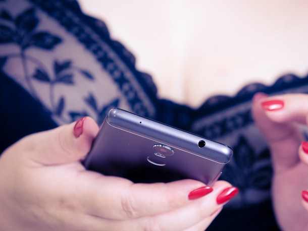 Plus size unrecognizable woman wearing black lace soft bra using cell phone. Female in lingerie texting on smartphone.
