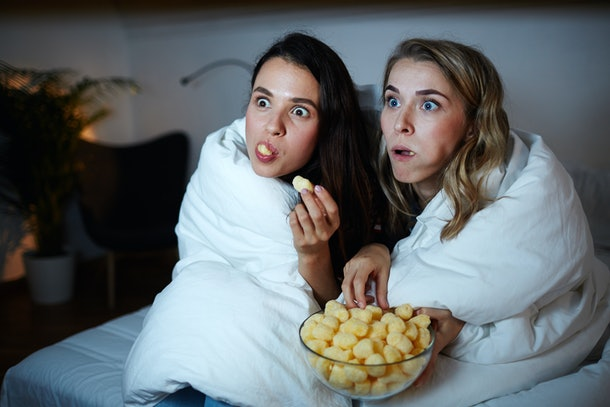 Two girls eating corn rolls from a glass bowl while watching a movie at night in bed.