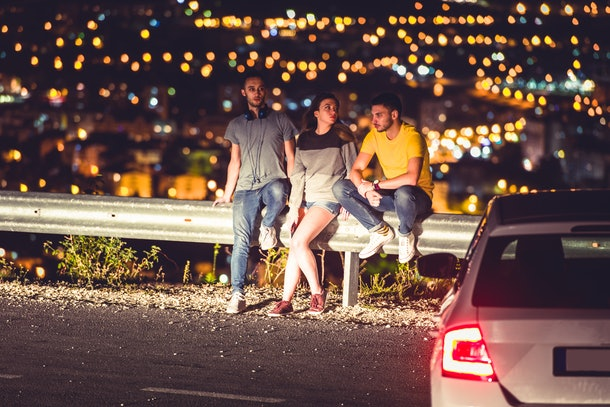 Friends at night are standing near their car and enjoying the view and the city lights in the summer nights