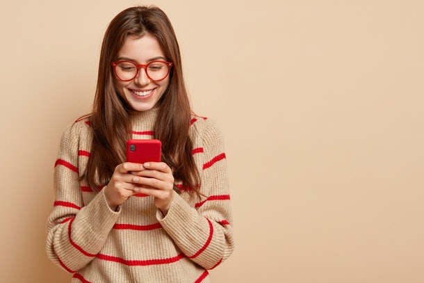 Indoor photo of satisfied teenage girl texts on cellular, reads interesting article online, wears casual outfit, creats new publication on own web page, isolated over brown studio wall with free space