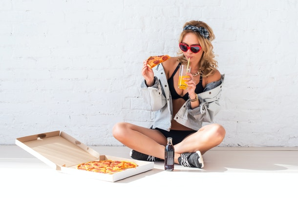 Young woman eating a piece of pizza drinking juice sitting on floor wearing sunglasses