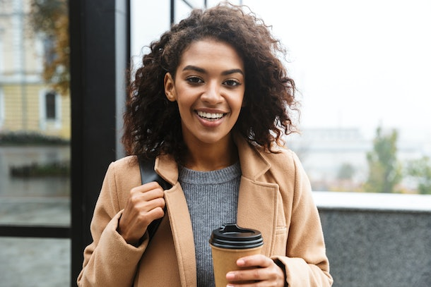 A young woman with a tan coat walks outdoors and holds a to-go coffee cup in her hand.