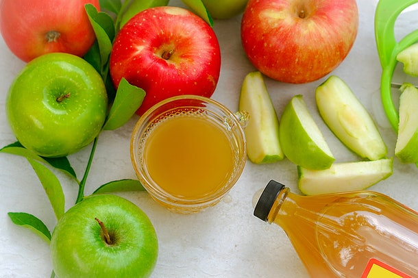Apple cider vinegar in a glass cup in the middle of red and green apples with the bottle near by. Drinking apple cider vinegar has a lot of health benefits.