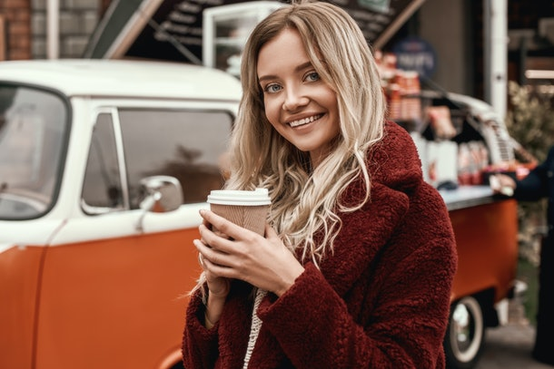 A blonde woman with long hair and red fluffy coat poses with a drink in hand in the fall.