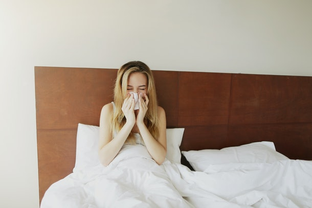 Female sick Woman sneezes in white bed with napkin Sunlight , get cold outside. Concept of pills medical treatment advertisement