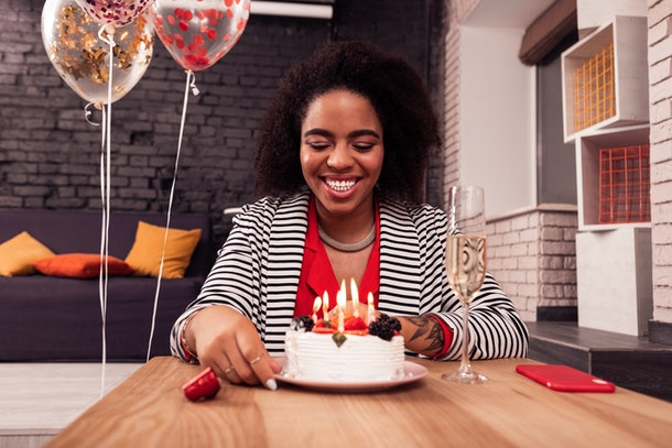 So hungry. Cheerful nice woman looking at her birthday cake while wanting to eat it