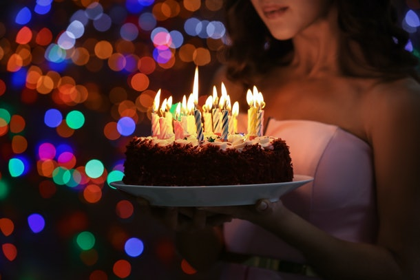 Young woman holding plate with tasty birthday cake against defocused lights