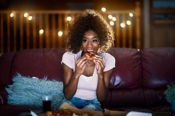 woman eating pizza and watching tv late at night on sofa