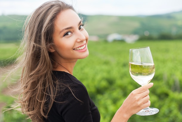 A young brunette woman smiling and holding up her glass of wine at a vineyard in the fall.