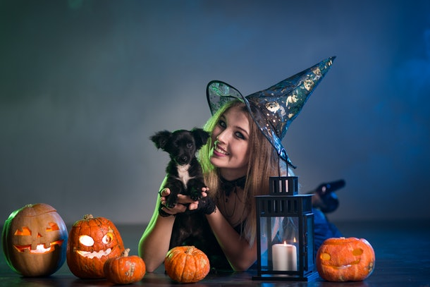 A woman dressed in a witch costume holding her dog, surrounded by pumpkins on Halloween.