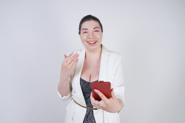 charming mix race plus size woman in a white business jacket standing with smart phone in hand on white background in Studio
