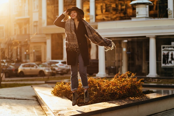 Enthusiastic girl in black coat and hat expressing happiness. Outdoor portrait of beautiful lady wears long scarf in autumn.