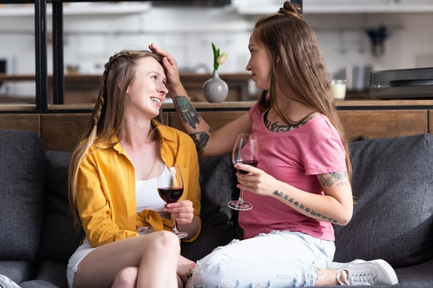 two lesbians holding wine glasses and looking at each other while sitting on sofa in living room