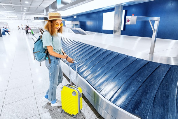A woman in jeans, sneakers, sunglasses, a T-shirt, and hat waits at baggage claim with her yellow suitcase.