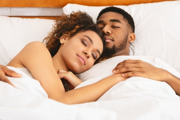 True love. Young african lovers sleeping together, cuddling in bed, closeup
