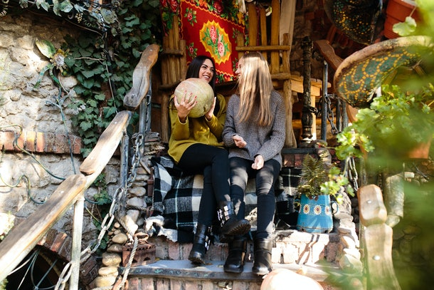 Two girls in sweaters, leggings, and boots sit on wooden steps in the fall.