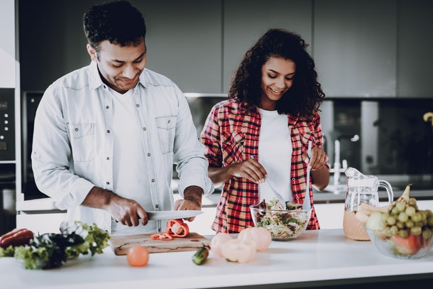 A happy couple cooks and prepares food in a kitchen.