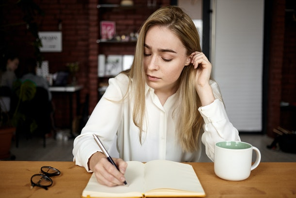 Candid shot of attractive blonde student girl in white blouse doing homework at workplace at home, writing down in open copybook, drinking tea, having serious concentrated facial expression