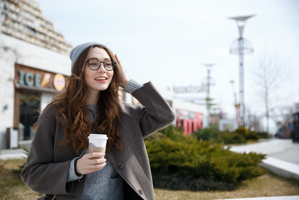 Smiling cute young woman walking and drinking take away coffee outdoors