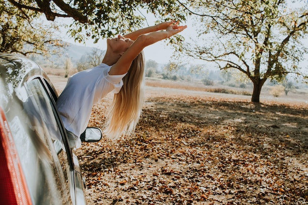 A happy blonde woman sticks her head and arms out of a parked car in the fall foliage.