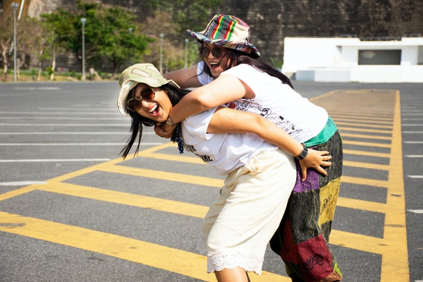 A mother and daughter laugh and smile in a parking lot.