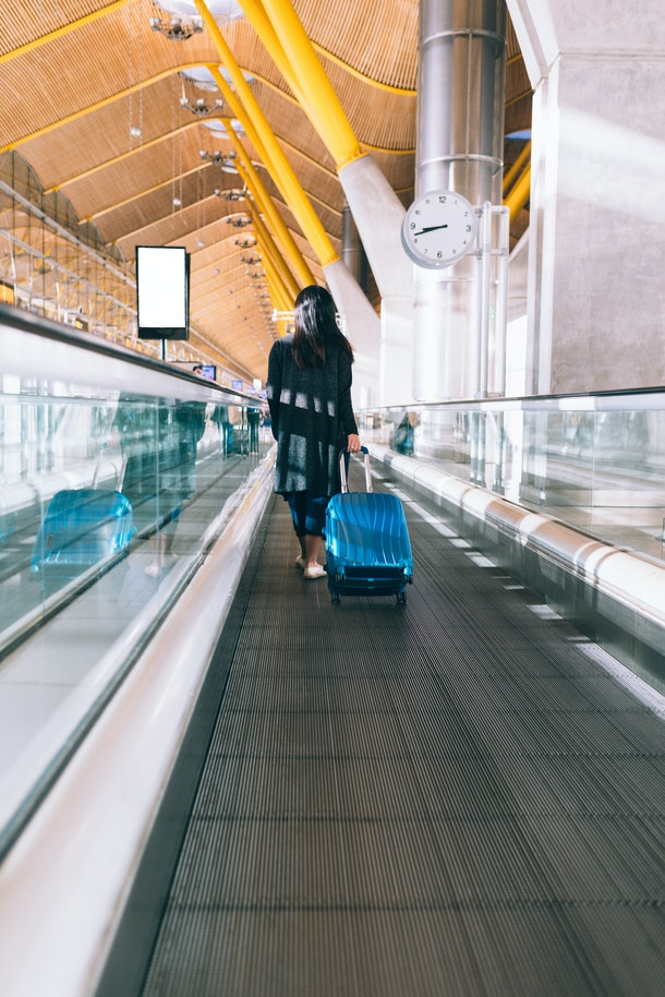 A brunette woman pulls her suitcase and walks on a moving walkway in an airport.