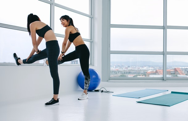 Two females stretching legs by a window and talking. Happy women stretching and relaxing their leg muscles after exercising in fitness studio.