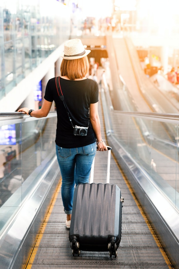 A woman dressed in jeans, a black T-shirt, and a hat pulls her suitcase in the airport.